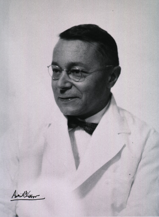 <p>Head and shoulders, left pose; wearing white coat and glasses.</p>