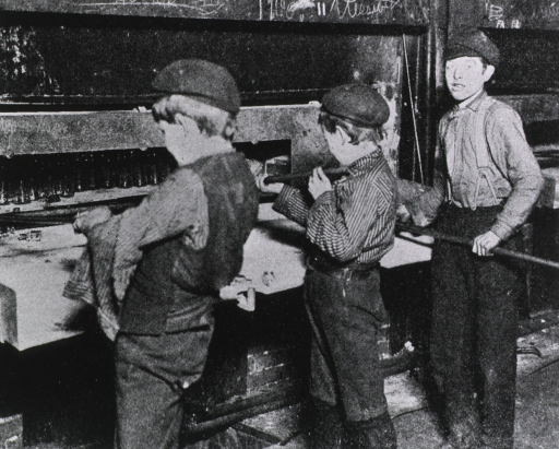 <p>Interior view: three young boys are standing before a furnace in a glass factory.</p>