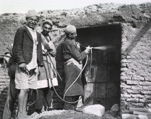 <p>Two men smile and hold a hose, while a third holds the nozzle and sprays the closed entrance of a brick hut.  A fourth man stands amidst the others and smiles at the camera.</p>