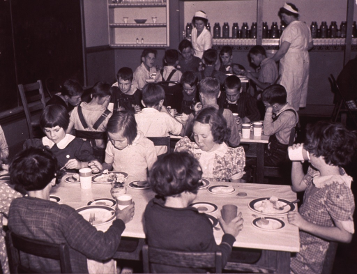 <p>Children are eating lunch in a school cafeteria; cafeteria workers are standing in the background.</p>