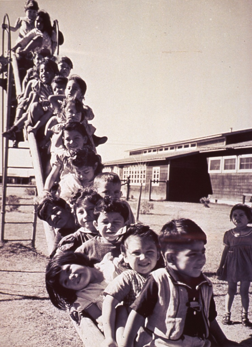 <p>A group of children lined up on a slide on the playground at Robstown Camp, Texas.</p>
