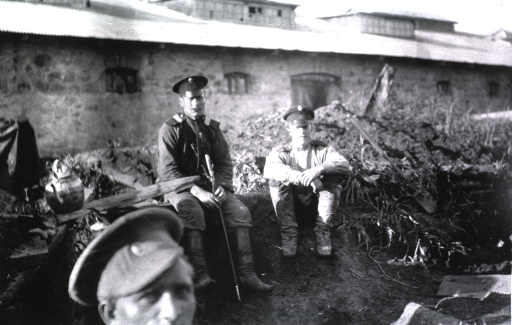 <p>Convalescents in military uniform sit outside the hospital on a mound of dirt, grass, and twigs.</p>