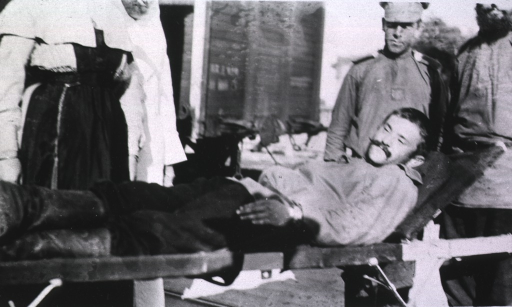 <p>A patient, lying on a litter, is surrounded by a nurse and two medical personnel.</p>