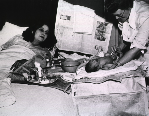 <p>Bedside scene, a nurse demonstrating infant care to a new mother.</p>