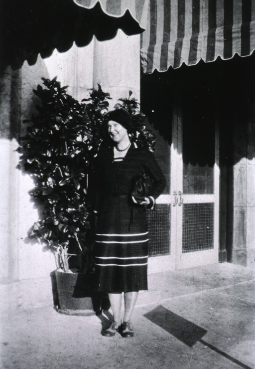<p>Standing, full-length, in front of a potted tree in beside a building.</p>