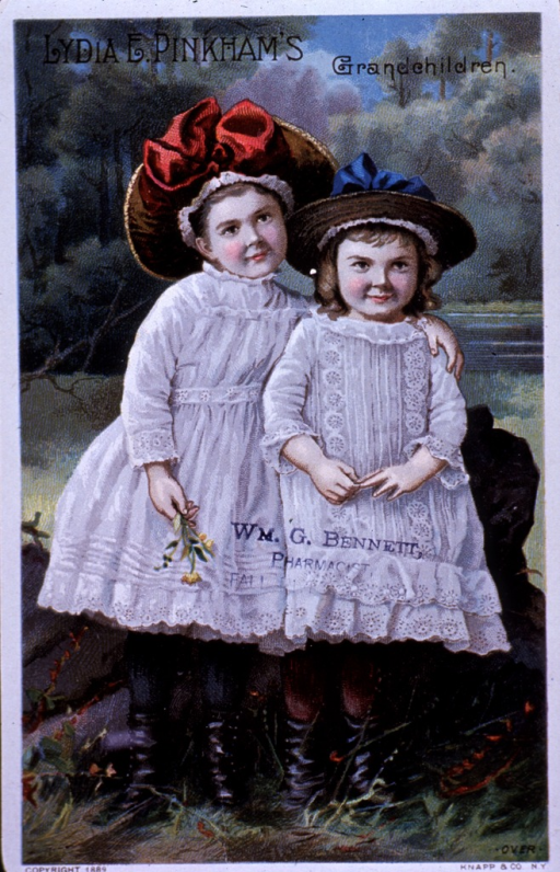 <p>Visual motif:  Outdoor scene showing two children standing together, wearing dresses and hats; one child with arm around the other and holding flowers.</p>