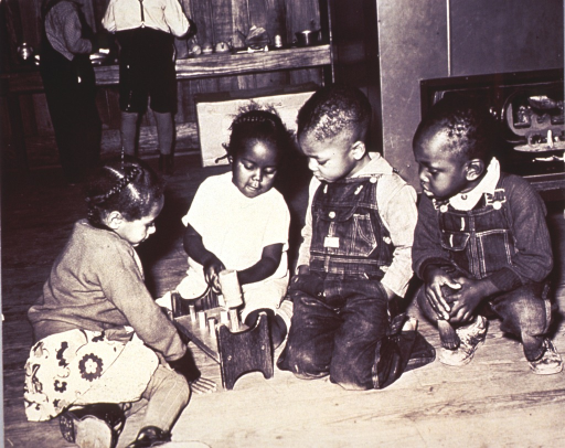 <p>African American children are playing with a wooden hammer and peg set.</p>