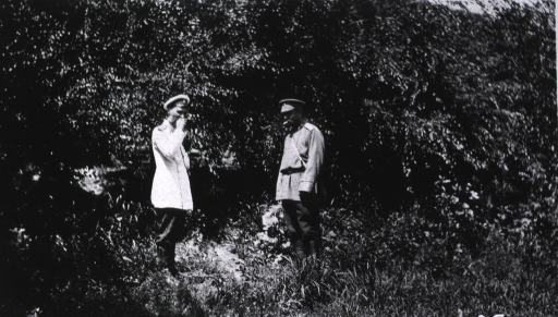 <p>Two senior physicians at Military Hospital No. 2 standing by the trees and bushes.</p>