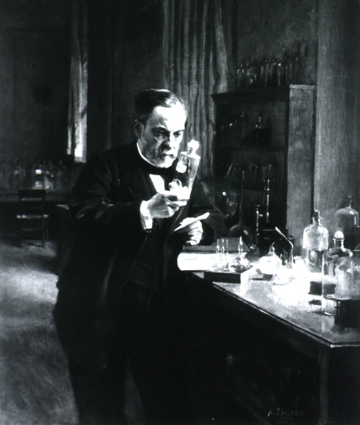 <p>Three quarter length, standing, in his laboratory, examining a glass bottle.</p>