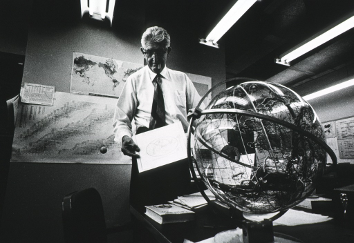 <p>Three quarter length, full face (head slightly downward); smoking cigar; standing in Radiation Biol. Lab. at UCLA, in back of a transparent globe of the world; holding map, others on wall.</p>