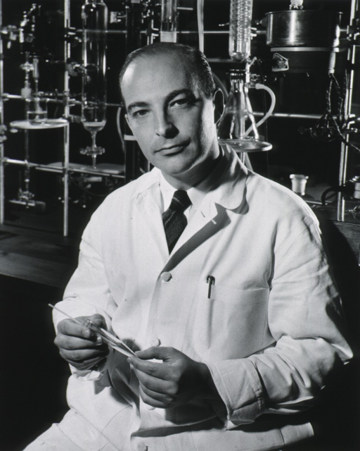 <p>Half-length, seated in laboratory, full face; wearing white lab coat; glassware apparatus in background.</p>