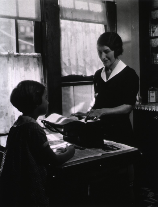<p>View of a nurse in a patient's home.  The nurse is removing something from her bag in preparation for an examination as a little girl watches.</p>