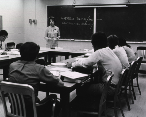 <p>Interior view: Classroom with instructor standing in front of the blackboard; indexers and MEDLINE search analysts are sitting around the tables.</p>