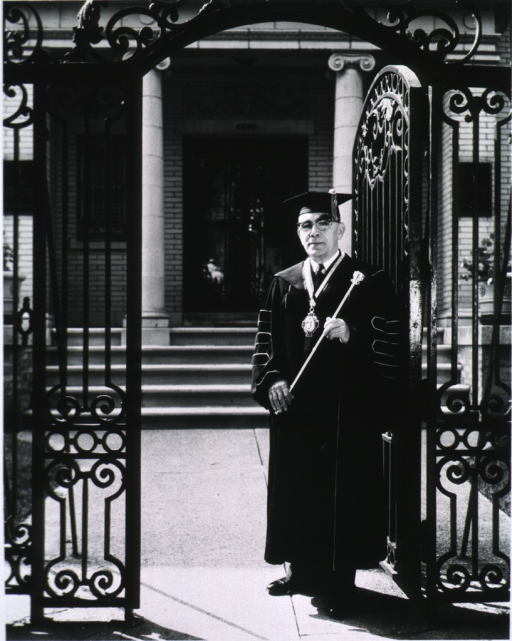 <p>Full length, standing, wearing academic cap and gown, holding a mace.</p>