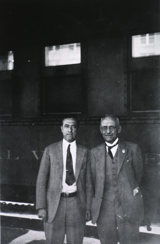 <p>Three-quarter length, standing beside railway car with Dr. Post, full face.</p>