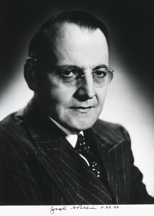 <p>Head and shoulders, seated, with face to right, wearing glasses.</p>