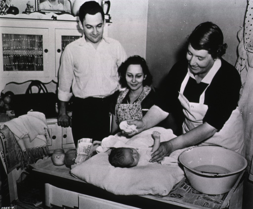 <p>Showing a member of the Visiting Nurse Association demonstrating proper infant care and bathing techniques to the parents.</p>