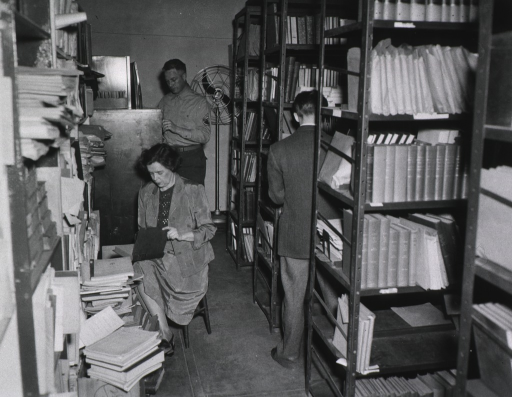 <p>Interior view:  Material is in the stacks, piled on the floor, and on shelves against the wall.</p>