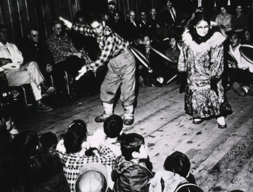 <p>An Eskimo man and an Eskimo woman dance while several men beat drums; many people look on, children sit in the foreground.</p>