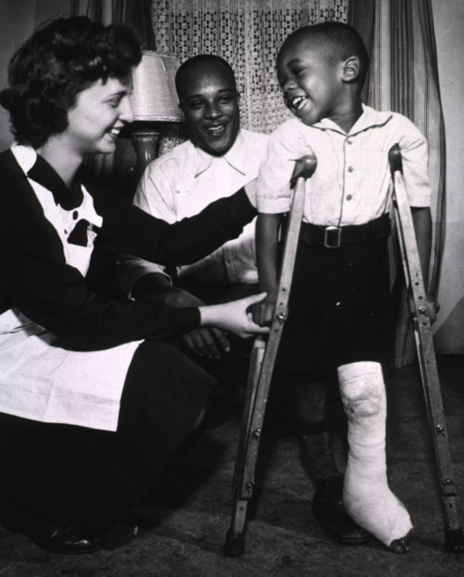 <p>A young boy, on crutches, his left leg in a cast, takes first steps with the aid of a Public Health nurse.</p>
