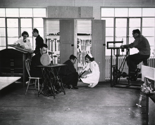 <p>Four men are at work in a woodshop.  Two female nurses assist them.</p>