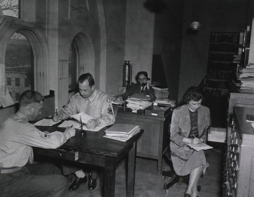 <p>Interior view: Gertrude Hutton is sitting by the card catalog and Charles Roos is on the telephone at his desk.  Military personnel are sitting at table.  There is a book shelf against the back wall.</p>