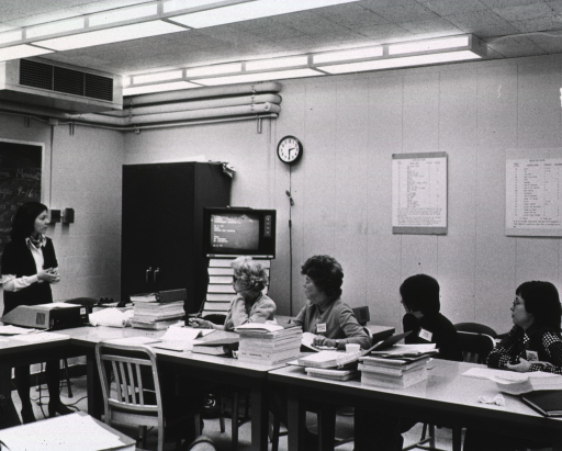 <p>Interior view: Thea Fishcer is joined by three other colleagues in a Bibliographic Services Division training class taught by Patti Burmeitser.  A television, serving as a monitor, is on top of a stack of books; the keyboard and modem are in front of Patti Burmeister.</p>