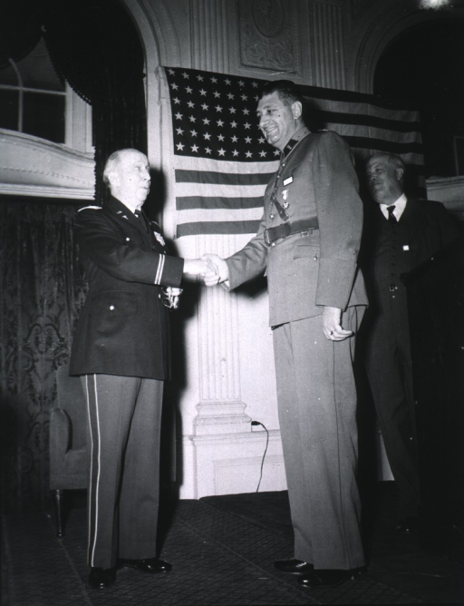 <p>Wearing dress uniform (Colonel), shaking hands with foreign officer.</p>