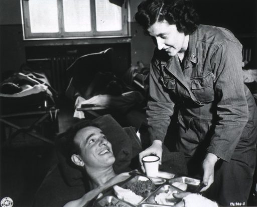 <p>Three-quarter length, left pose; offering food to a wounded soldier on a cot.</p>