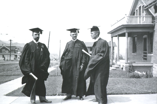 <p>Full length, standing, wearing cap and gown; with Drs. Crisp and Libby.</p>