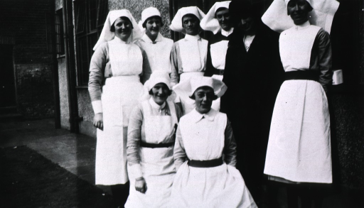 <p>View of Hickcox and seven nurses standing next to a building.</p>