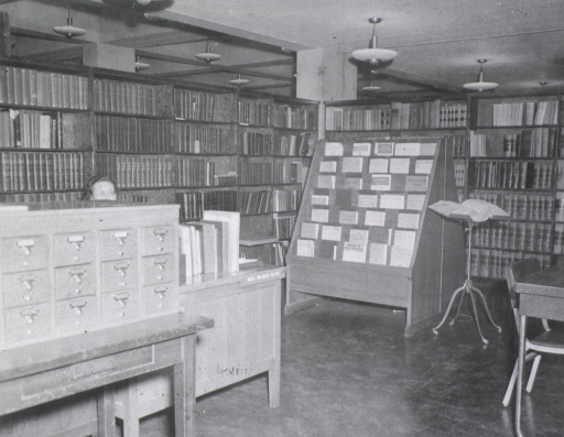<p>Interior view of the Surgeon General's Reference Library in the Pentagon:  A card catalog is sitting on a table in front of Mildred Blake's desk.  Serials are on display in front of the stacks which are at a right angle in the background.  A dictionary is on a stand next to the serials.</p>