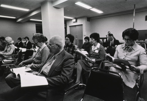 <p>Interior view: People are sitting in arm chairs with material in their laps in a large room.</p>