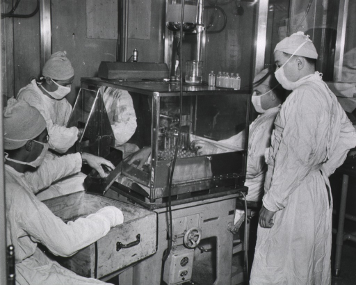 <p>Four men in lab gowns, head coverings, and masks are working with a machine to create ampules of typhoid vaccine; two of the men are wearing rubber gloves.  A drawer with ampules is sitting on a table in front of one of the men.</p>