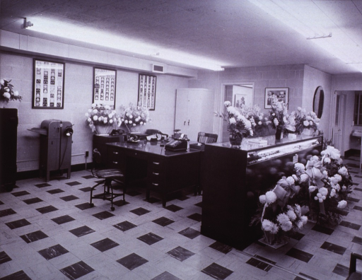 <p>Interior view: glass top counter displaying dentures is surrounded with flowers; an adding machine and telephone are on top of a desk; a mimeograph machine; fluorescent lighting; linoleum floor; a window with venetian blinds and a sink are in background.</p>