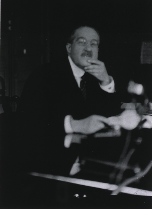 <p>Seated. Monsier J. Alquier in his office at the laboratory of the Societe Scientifique d'hygiene Alimentaire.</p>