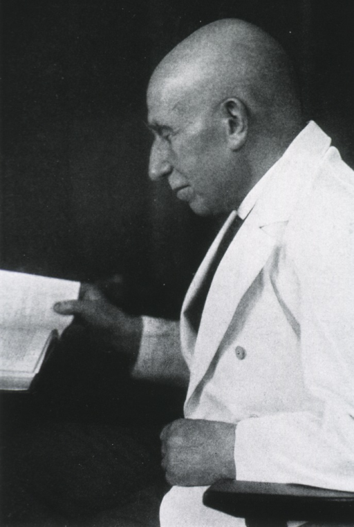 <p>Half-length, seated, left profile; reading; wearing white coat.</p>