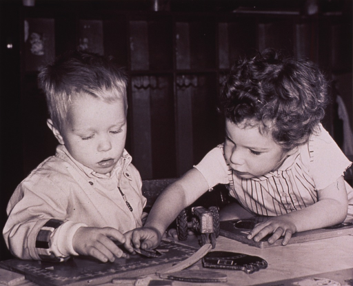 <p>Two small children are playing with wooden puzzles.</p>