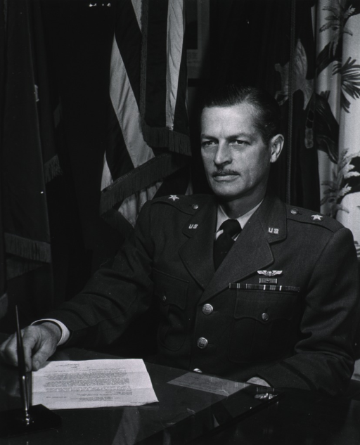 <p>Half-length, full face, seated at desk, on hand resting on desk top, wearing uniform of U.S. Air Force MC Brigadier General.</p>