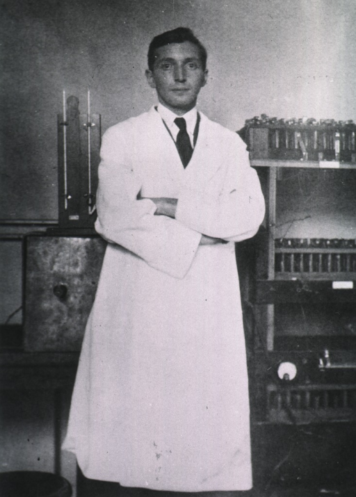 <p>Three-quarter length, full face, wearing a lab coat, arms folded across chest, standing in front of lab equipment.</p>