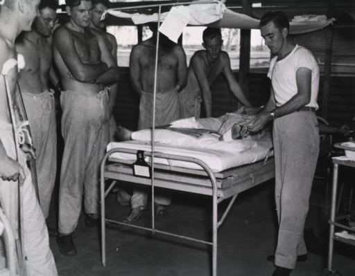 <p>Shirtless servicemen stand next to a bed in a ward and watch the wardmaster treat the feet of a patient who lies in the bed.</p>