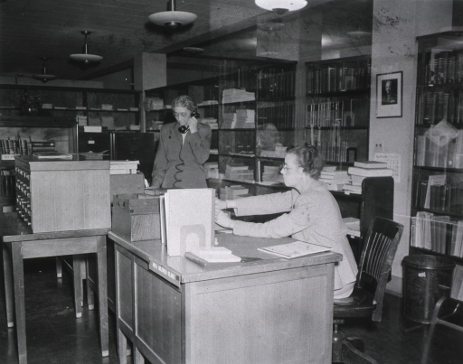 <p>Interior view:  The stacks are in the background and behind the desk.  A catalog is on the table.  A glass enclosed bookcase is next to file cabinets.  The photo is a double exposure with the image of a man's face between the two women.</p>