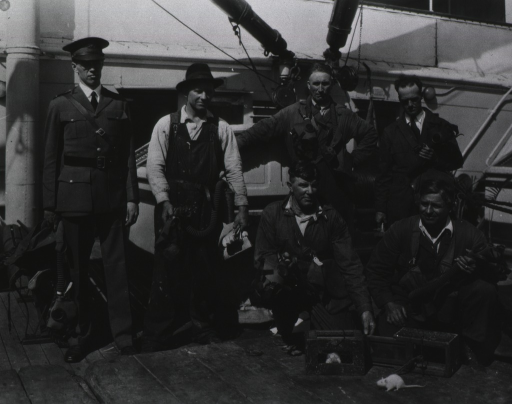 <p>A group of men carrying gas masks are on board a ship; one man, an officer, is wearing a uniform; white rats, in the foreground, are used to test compartments after fumigation.</p>