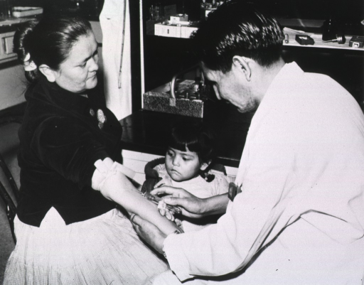 <p>A man is drawing blood from the right arm of a woman sitting in a chair at a medical facility; a young girl observes.</p>