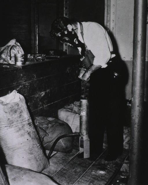 <p>A man wearing a gas mask is using a handpump to force calcium cyanide dust into known rat harborage; the man's uniform cap sits on a bench nearby.</p>