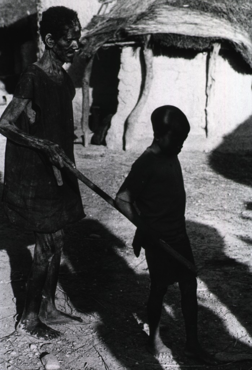 <p>A man holding one end of a stick is being led by a child holding the other end of the stick; village huts are in the background.</p>