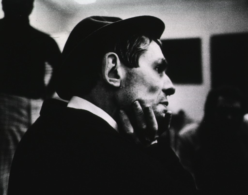 <p>Close-up of a depressed-looking man wearing a felt hat, his chin propped in his right hand, staring off into space.</p>