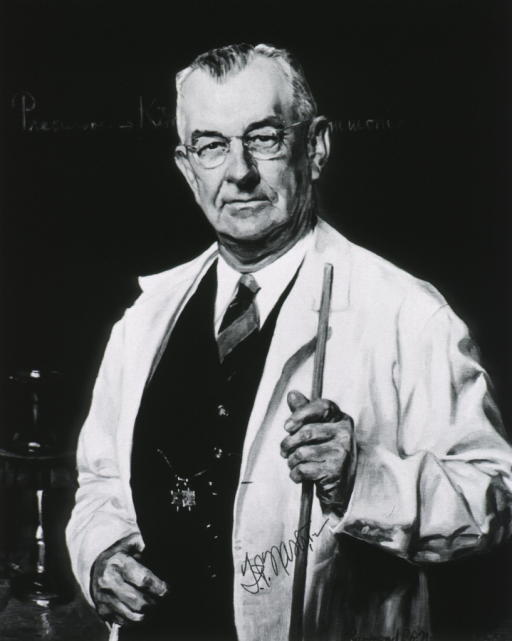 <p>Half length, standing at black board holding pointer and wearing white coat.</p>