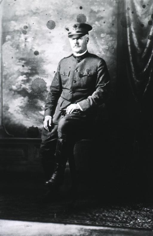<p>Full length, seated on table; in uniform.</p>