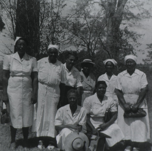 <p>View of eight African American nurse midwives, one of whom is Deola Cyrus, at a midwife meeting, Clinton, Louisiana, about 1955.</p>
